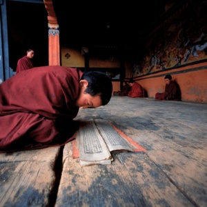 A young monk learning his prayers at the entrance to a chapel in Bhumthang (Bhutan)