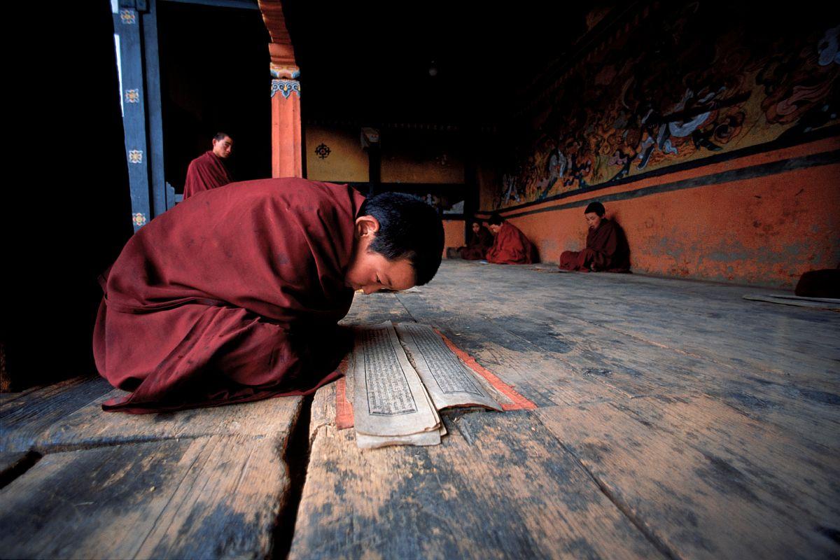 Un jeune moine apprend ses prières at l'entrée d'une chapelle au Bhumthang, Bhoutan