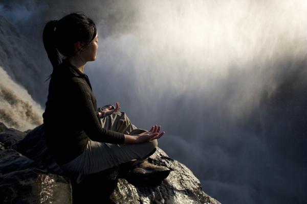 Varunee, adepte de yoga et de méditation, au sommet des chutes de Dettifoss en Islande