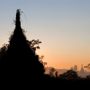 In Sittwe, to the West of Myanmar, two young women take a walk near a stupa covered by jungle vegetation.