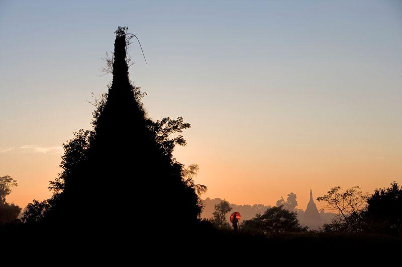 A Sittwe, à l'ouest du Mynamar, deux jeunes femmes se promènent auprès d'un stupa recouvert par la vegetation de la jungle voisine