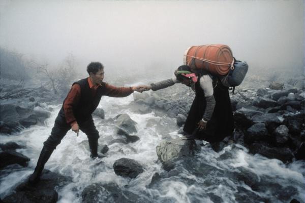 A villager from the Kham helps a woman carrying goods to cross a mountain torrent. (Tibet)